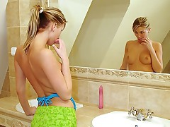 A teenage girl with a ponytail is admiring herself in the mirror. Slowly stripping all of her clothes off she strokes her body gently. The she steps into the baths and uses the water to massage her pussy before sticking a large marital-device into it.