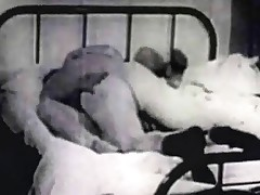 A janitor of an apartment building is sweeping the hallways and peeps through the keyhole of one of the doors. In the room behind it a couple is on the bed. The woman gives the guy a quick suck before they start fucking.