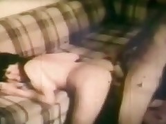 A angel in bikini is sitting on a couch. A dude next to her is giving a kiss her tits and rubbing her body all over. He takes out one of her tits and licks the nipple. A little later she bends over the couch so he can fuck her from behind.