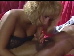 A nearly naked guy is laying on a sofa where a blonde angel in black lingerie is giving him a blow job. He is touching her wet crack up at the same time. She keeps on sucking him and is playing with her tits too.