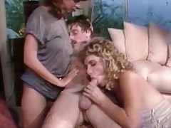 A golden-haired girl is laying on the floor where a chap is fucking her hairy pussy. A little later he is sitting on a stool with the girl on his lap. A second girl has joined them and she is stroking the first girls behind.