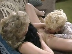 A blonde girl is leaning back in a wicker chair. She has her legs spread wide and another woman is licking her hairy pussy. Spreading the pussy lips she begins to massage the other beauties clit with her thumb.
