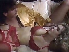 A chap and a blond beauty are lying down on the couch. She is only wearing a red bikini. He strokes her body all over and kisses her crotch. The beauty then sucks the guy's long dick while he rubs her pussy before he starts to fuck her from behind.