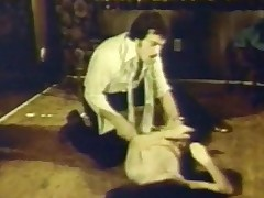 A man and a woman are on the floor of the living room. He is forcibly removing her clothes while she protests in a loud voice. When she is naked, the guy fucks her hard, folding her legs against her chest to penetrate her deeper.