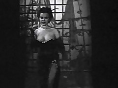 In this black and white movie from the 1950's we see a young woman in an evening dress enter a stage where this babe begins to dance around. She removes her dress and shows her large whoppers off. Later on this babe plays with her naked breasts.
