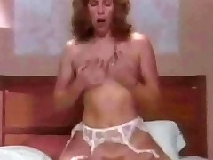 In a spoof on All in the Family, Edith Bunker lets a man into the living room. A few minutes later she is blowing his dick in the bedroom and then fucks him too, taking his dick all the way into her trimmed pussy.