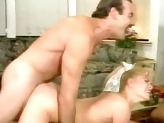 A blonde girl is sucking the schlong of a guy who laying down on a couch. At the same time a second guy is fucking her hard from behind. The 3 of them move to the floor and the guys trade places, fucking the girl in her love tunnel and her mouth.