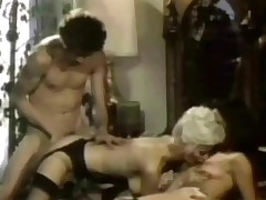 A blonde girl and a guy are kissing every other whilst a second girl is watching them. The first girl lays down on the bed too and licks the ther girls love tunnel whilst the guy is fucking her from behind in her hairy pussy.