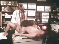 A guy is leaning with his behind against a desk while a girl is sucking his dick. A second girl is on the floor, licking the first girls pussy. The first girl lays down on the copying machine to get fucked by the guy.