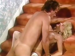 A naked blonde girl in white stockings is kneeling on the stairs where a stud is fucking her hairy pussy from behind. After a during the time that she turns around and lays down on her back. The stud then fucks her some more.