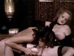Two women, one dark haired and the other blonde, are in a bedroom. The blonde girl orders the other one to undress. Then she lowers her top and plays with her large tits. Then the brunette hair licks the blonde girls pussy.