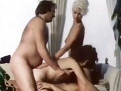a couple is laying down on the sofa fucking each other while a second girl is licking the first ones pussy. Then the first girl climbs on top of the chap and lowers herself over his dick. A second chap joins them and fucks the girl in her ass at the same time.