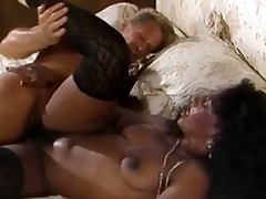 A white guy and a black woman are fucking on a bed. She has one leg raised up high. The guy moves her into some other position and then she goes down on all fours so he can fuck her ass until he comes on her behind.